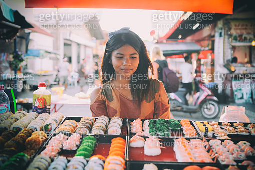 Beautiful Thai girl sells Various kinds of sushi served in street Thai market