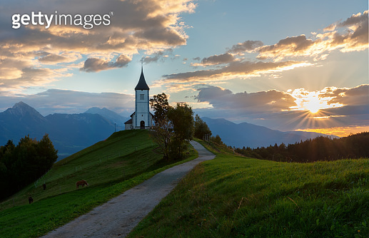 Church on the hill at night.Beautiful scenery at Jamnik, Slovenia. Panoramic view of the Alps behind the church.