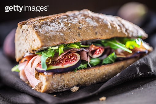 Sandwich with figs prosciutto spinach arugula and cheese dip.
