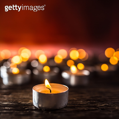 Many candles symolizing funeral religios christmas spa celebration birthday spirituality peace memorial or holiday burning at night.
