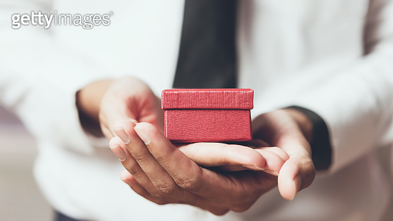 Man holding the empty red gift box.