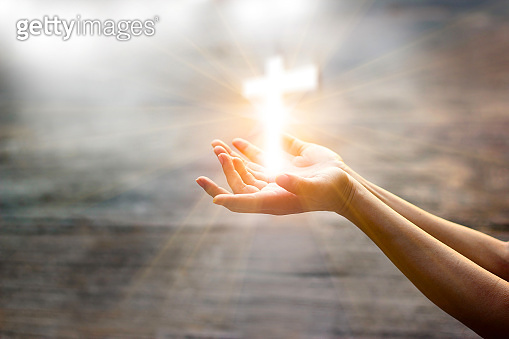Woman with white cross in hands praying for blessing from god on sunlight background, hope concept