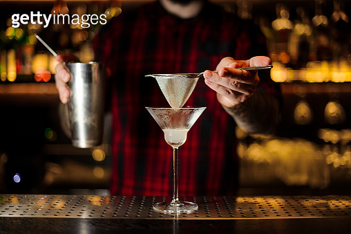 Bartender holding a steel cocktail shaker and sieve above the glass