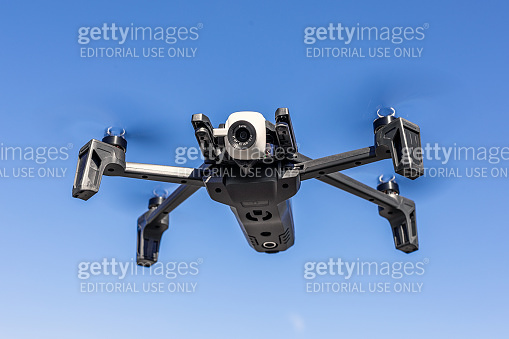 Parrot anafi drone flying against blue clear sky on background on bright sunny day.