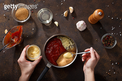 Hands put mustard in the saucepan for cooking bbq sauce.