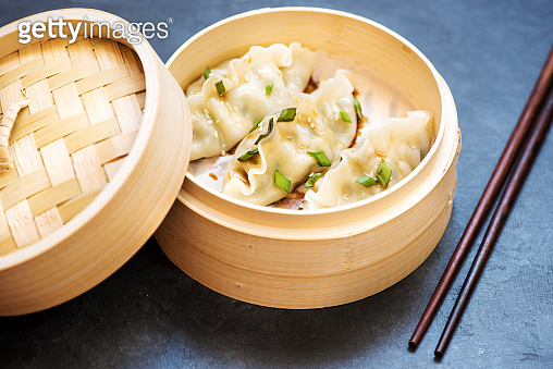 Steamed dumplings in bamboo steamer and chopsticks on a black concrete background
