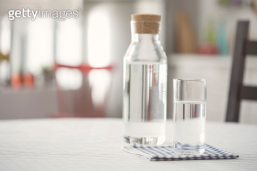 Water bottle and glass of water on kitchen table