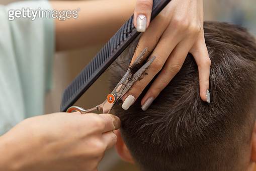 close up of hands of young barber making haircut to attractive man in barbershop