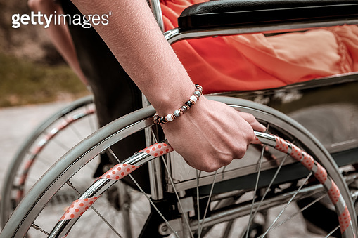 Person with disability sitting in the wheelchair and putting hand on the wheel