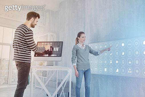 Cheerful programmer working on computer while his coworker standing near