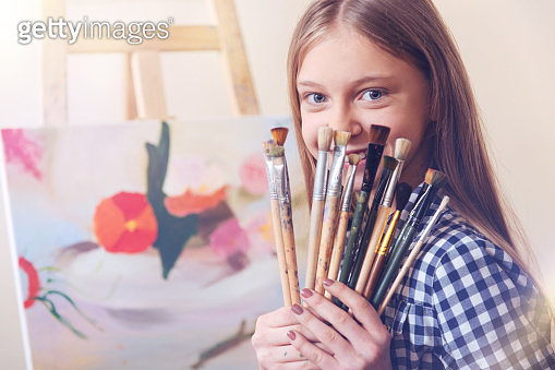 Talented young lady showing her set of painting brushes