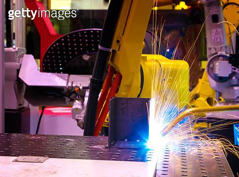 industrial yellow robot welder welding steel part manual, welding splatter repairman, light weld