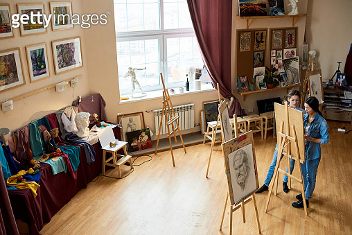 Artist teaching student in creative workshop