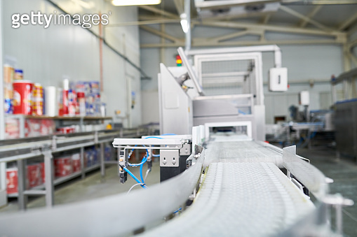 Modern production line with moving conveyor belt in food manufacturing plant