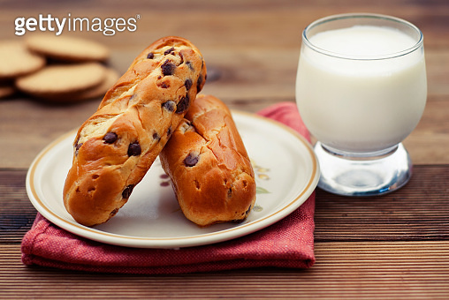 Traditional Buns with chocolate chips, breakfast or snack, rustic wood table.