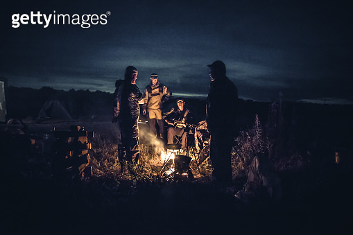 Group of men people travelers tourist resting camp fire in outdoors camp after long hunting day in the night