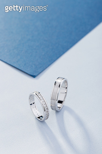 Pair of white gold wedding rings with diamonds in womens ring and matte surface in mens ring