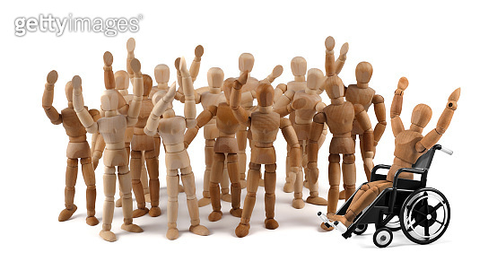 disabled wooden mannequin in wheelchair together with friends in a crowd
