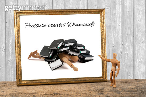 wooden mannequin motivating quotes - pressure creates diamonds - pushed down by ring binders