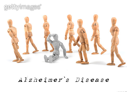 Alzheimer`s disease concept - wooden mannequin sitting confused in walking group
