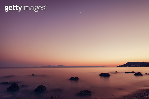 Landscape of sand and rocky shore. Beautiful seascape at sunset and blurred motion water