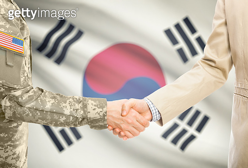 USA military man in uniform and civil man in suit shaking hands with adequate national flag on background - South Korea