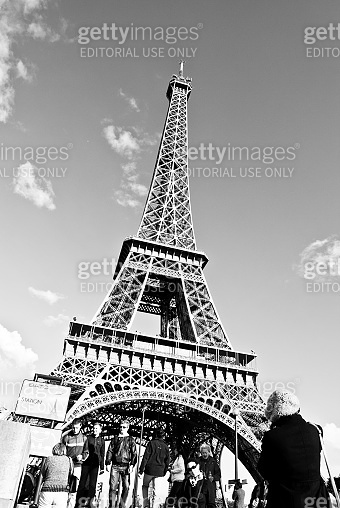 Tourists At The Iconic Eiffel Tower, Champ de Mars, Paris - France