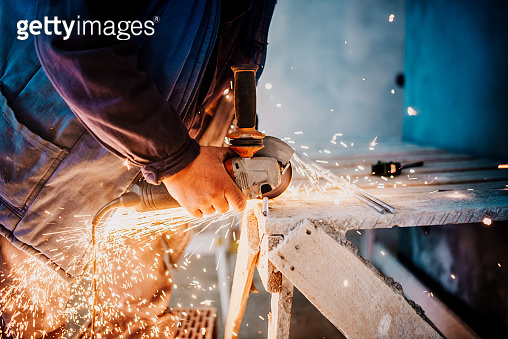 industrial workers hands cutting iron with angle grinder