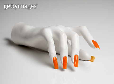 mannequin hand with perfect manicure and orange nail polish
