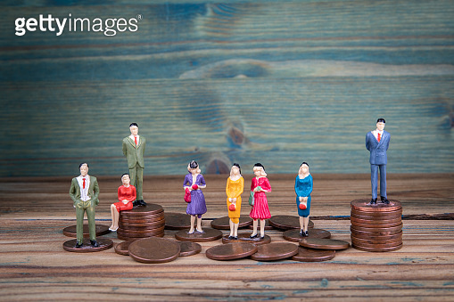 Miniature people standing on piles of coins