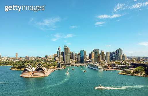 Stunning wide angle aerial drone view of the Sydney Harbour with the Opera House, a cruise ship and many skyscrapers in the background. Taken near the suburb of Kirribilli. New South Wales, Australia.