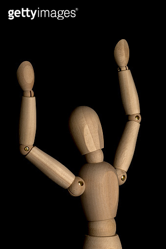 Business and Design Concept - Wooden Mannequin with Open Arm Gesture Isolated on Black Background