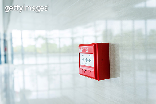 Red fire alarm on white wall