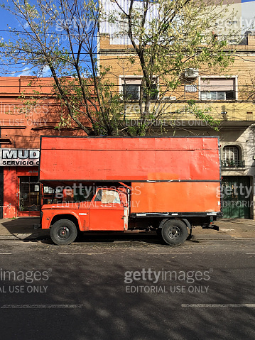 Old orange moving truck parked in the street