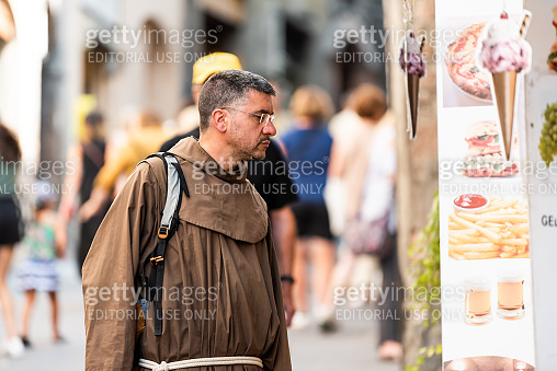 Monk priest religious man dressed in brown Franciscan cloth robe looking at restaurant fast food gelato and pizza menu in historic Umbria town village, gluttony sin temptation