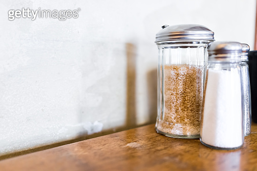Macro closeup of salt, pepper and brown raw sugar shakers in bottles on wooden table against wall in rustic restaurant