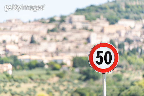Speed limit red 50 kilometers per hour km sign with bokeh background of town or village city of Assisi in Umbria, Italy cityscape during sunny summer day