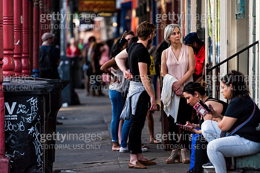 Frenchmen street sidewalk in Louisiana town, city, building, people tourists sitting by bars, colorful evening