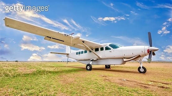 A white, single engine charter plane sits on a grass and dirt landing strip in a beautiful and remote location in Kenya.