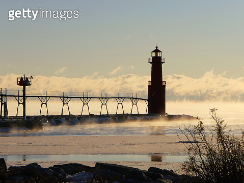 Lighthouse stands amid steaming Lake Michigan in Winter.