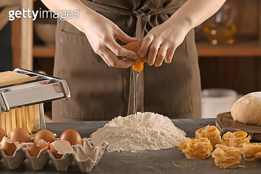 Woman breaking egg into flour at table. Pasta recipe
