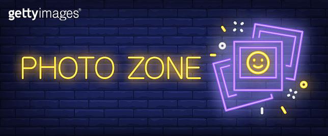 Photo zone neon sign. Instant photo on brick background