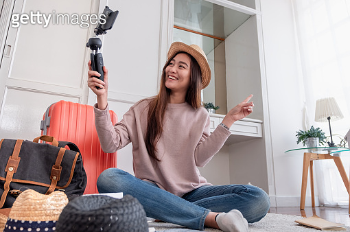 Asian young female blogger recording vlog video with mobile phone live streaming when travel.online influencer on social media viral concept.