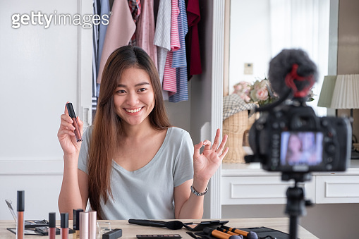 Asian young female blogger recording vlog video with makeup cosmetic at home online influencer on social media concept.live streaming viral.