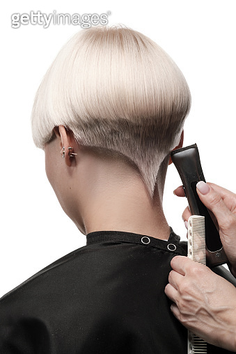 Hair coloring in blond. Preparation for hair cutting. Work stylist of the hairdresser in the salon on a white background.