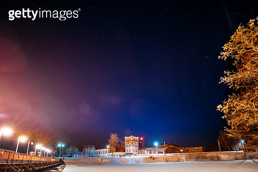Dobrush, Gomel Region, Belarus. Old Paper Factory Tower In Winter Night. Historical Heritage Under Night Starry Sky. Night Landscape With Natural Real Glowing Stars