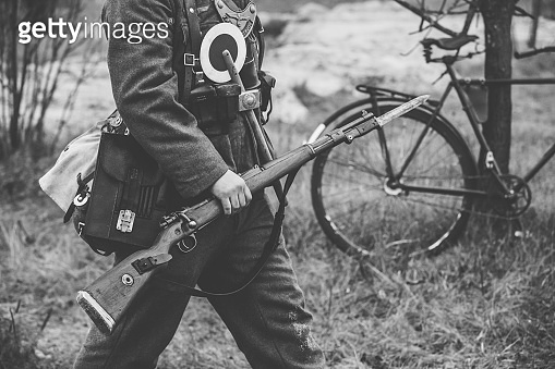 Re-enactor Dressed As World War II German Soldier Feldgendarm Holding Rifle. Photo In Black And White Colors. Soldier Holding Weapon. German Military Ammunition Of A German WW2 Soldier
