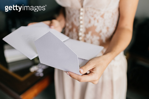 Female bride in white dress, holds white letter or envelope, prepares for invitation, prepares for wedding ceremony. Marriage concept