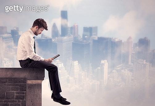 Sales person sitting on top of a tall building