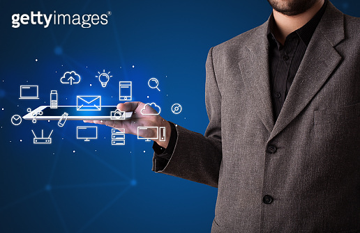 Businessman holding tablet with media graphics